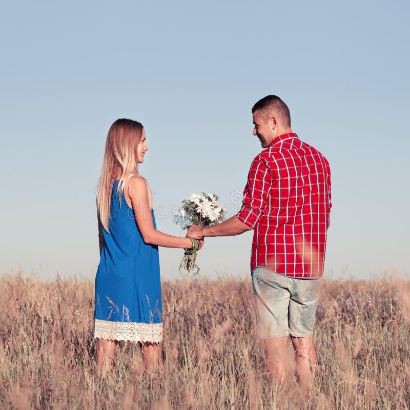Storia di amore Belle giovani coppie che camminano nel prato, all'aperto fotografie stock