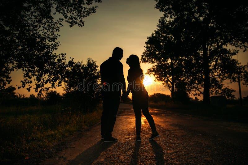 Storia di amore Coppie sul tramonto Siluetta immagini stock