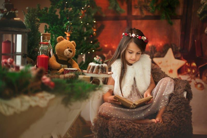 Storie colte castane di Natale della bella bambina al suo orsacchiotto del giocattolo fotografia stock
