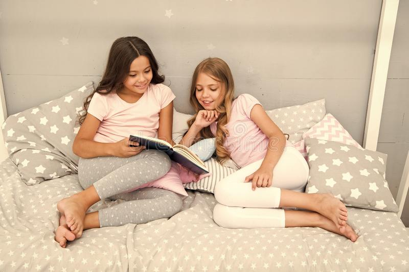 Stories every kid should read. Children read book in bed. Girls best friends read fairy tale before sleep. Reading. Before bed can help sleep better at night stock image