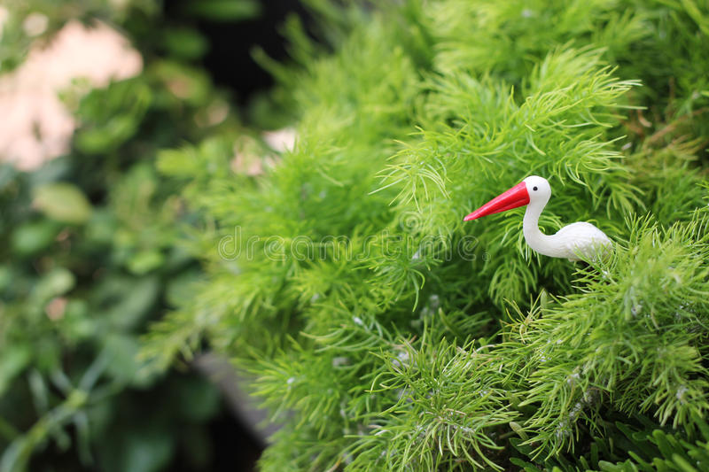 Stork garden statue with little garden background royalty free stock photography