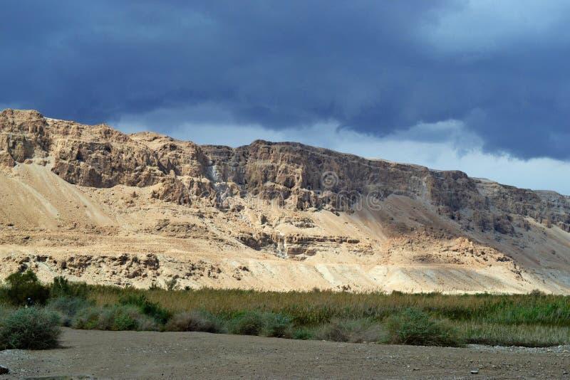 Storm över berget Masada i den Judean öknen, Israel mörkt - blå himmel ovanför berget bredvid det döda havet arkivbild