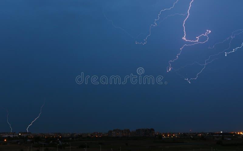 Storm över staden med flera blixt på natten arkivbilder