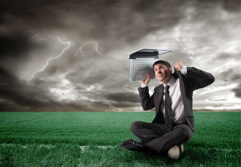 Storm. Businessman with laptop under a storm royalty free stock photos