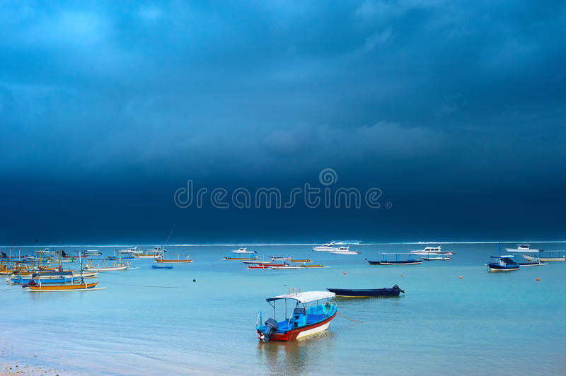 Storm on Bali island, Indonesia. Lots of fisher boats in the ocean in the strom. Bali island, Indonesia royalty free stock images