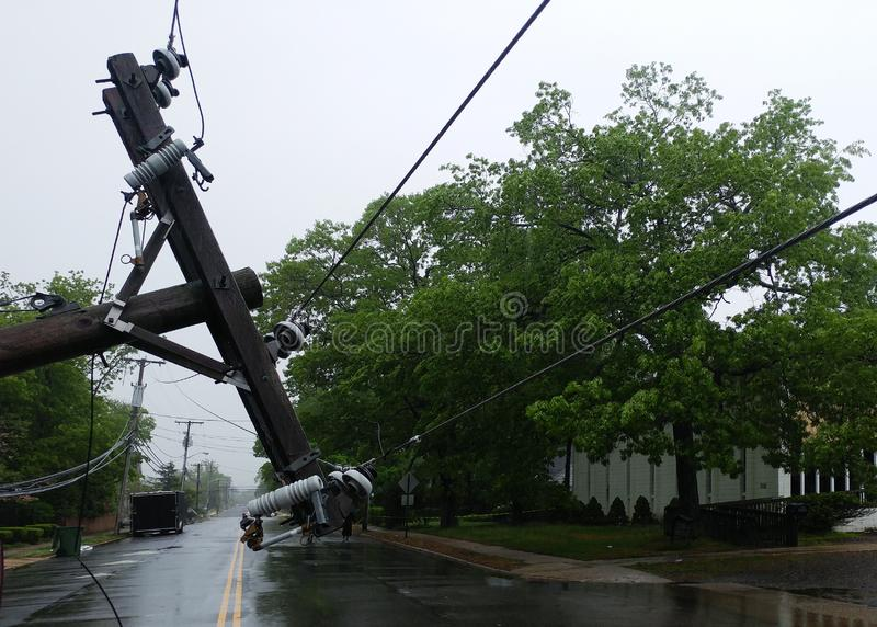 The storm caused severe damage to electric poles falling tilt. The storm caused severe damage to electric poles power lines over a road after Hurricanepoles stock photos