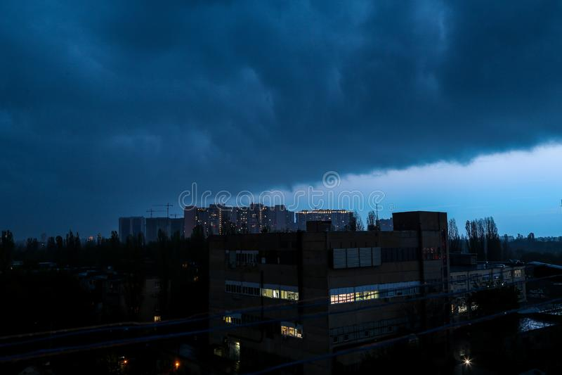 Storm in the city. Thunderstorm and rain outside the window. The sky is covered with dark clouds. Very dramatic weather. stock images