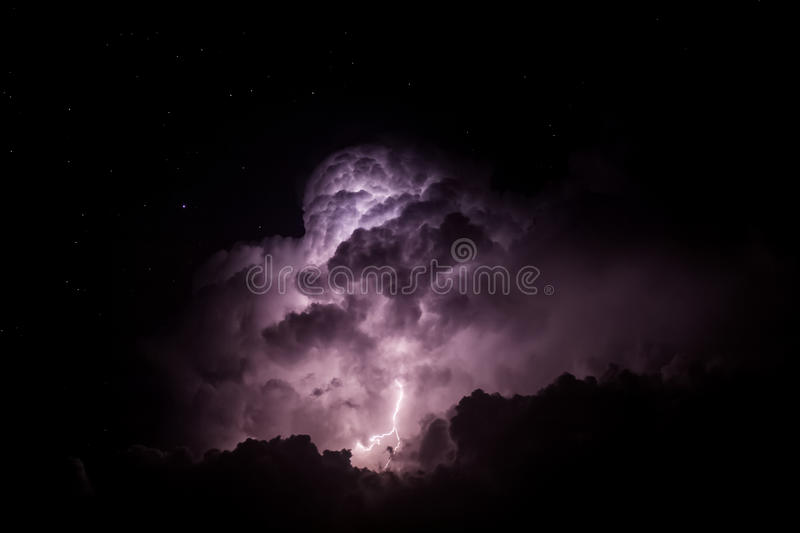 Lightning Illuminating Storm Clouds at Night. A lightning storm lights up the night with the stars visible behind stock photography