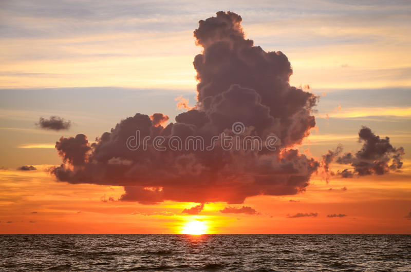 Storm Cloud over Setting Sun in Ocean stock photo
