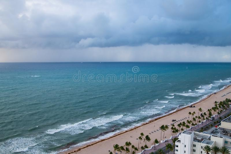 Storm clouds approaching tropical palm tree lined beach. Crews on the beach are cleaning seaweed from the sand. Storm clouds approaching tropical palm tree royalty free stock photo