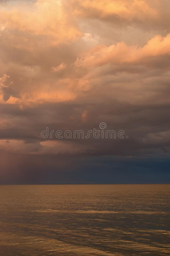 Storm clouds on the Azov Sea, illuminated by the setting sun, the sea horizon stock image
