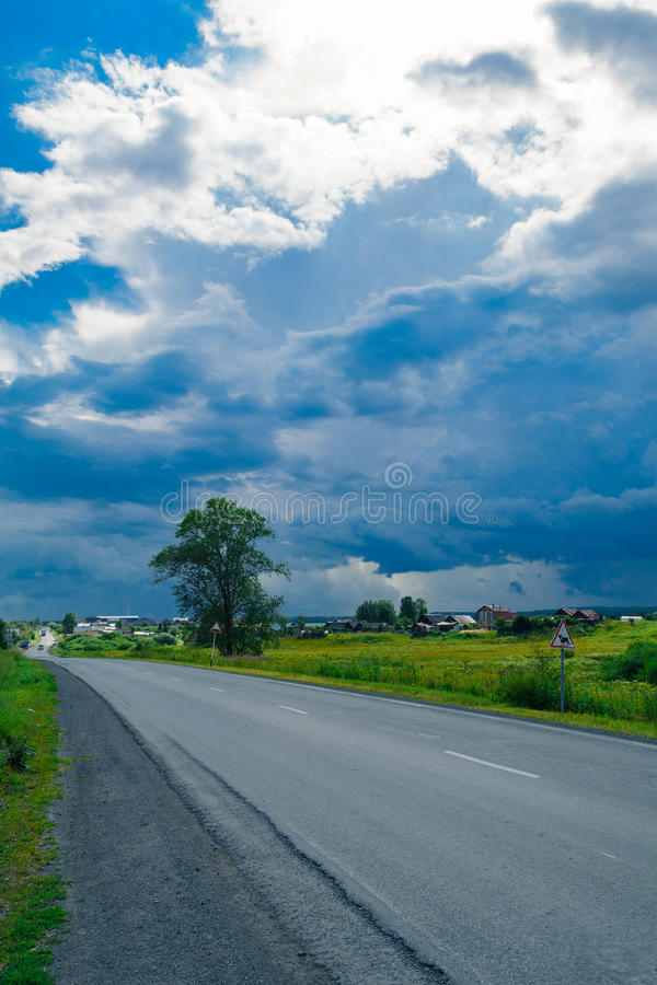 Storm clouds and blue sky near village stock photography