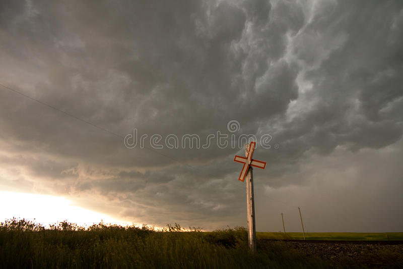 Storm Clouds brewing over railway crossing. In the prairies stock photography