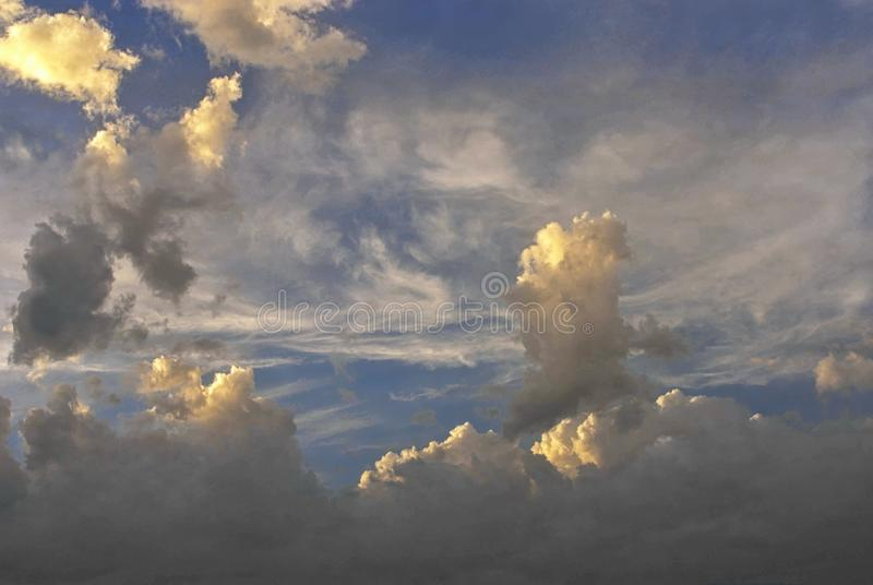Storm clouds form figures in the sky. The clouds have been transformed in minutes into new forms and were repeatedly covered by the sun`s rays royalty free stock photo