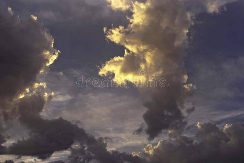 Storm clouds form figures in the sky. The clouds have been transformed in minutes into new forms and were repeatedly covered by the sun`s rays royalty free stock images
