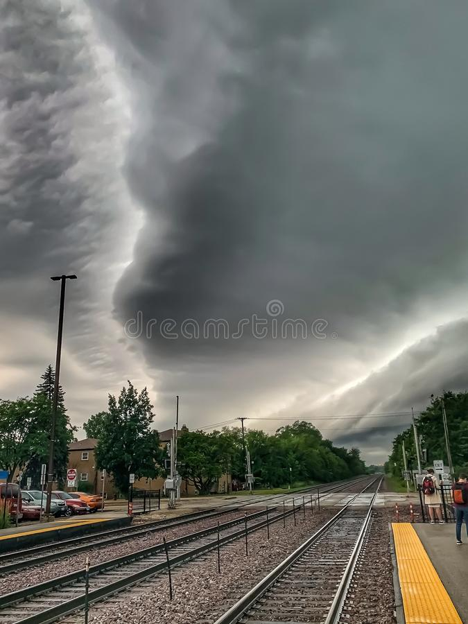Storm clouds form patterns over metra tracks and train station platform in Chicago area stock image
