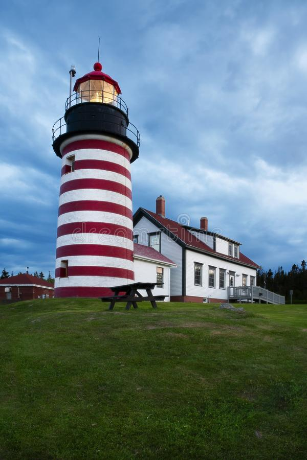 Storm Clouds Gather Around Red and White Striped Lighthouse in New England. Storm clouds gather as light shines brightly of West Quoddy Head lighthouse, a red royalty free stock images