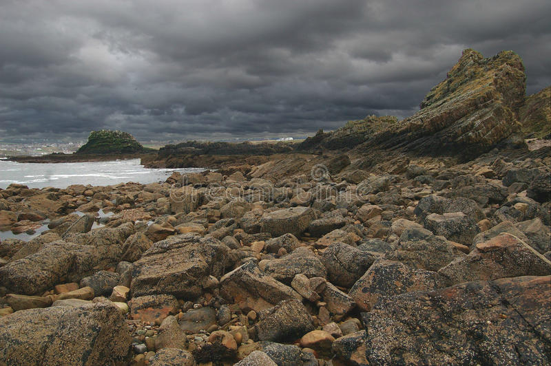 Storm Clouds Gathering over Rocky Shore stock images