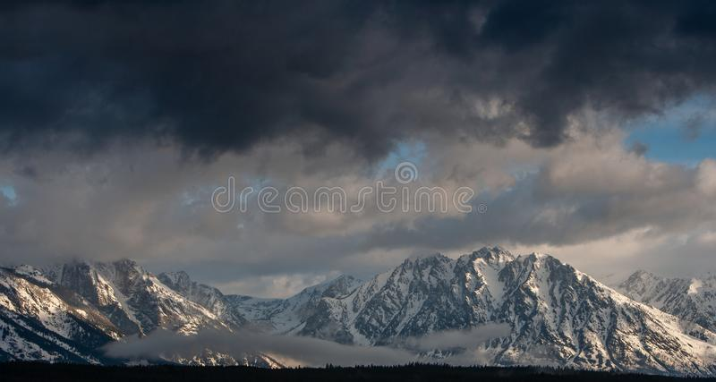 Storm clouds gathering over the snow covered Tetons in Wyoming. stock image