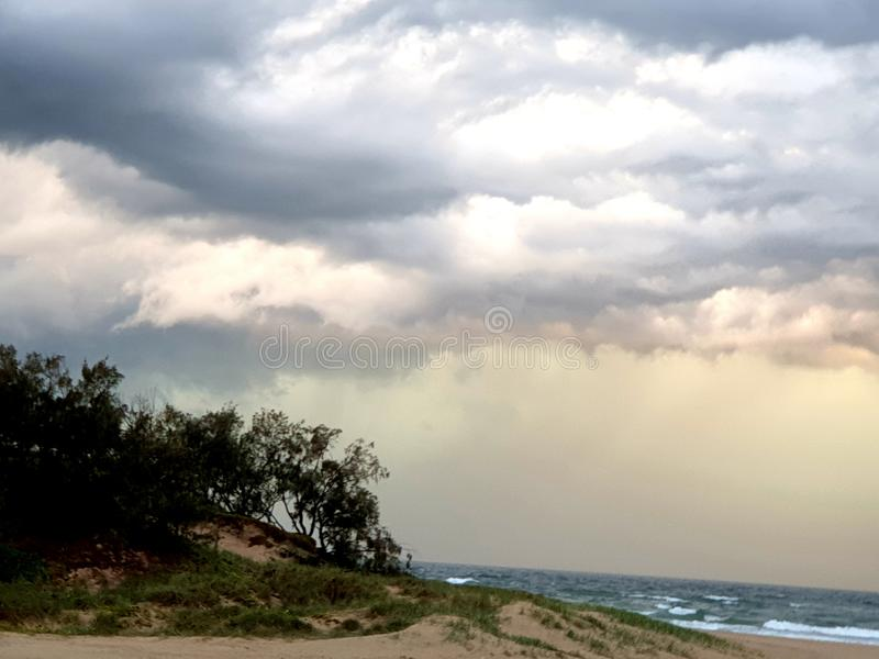 Storm clouds over bush beach trees and the ocean stock photos