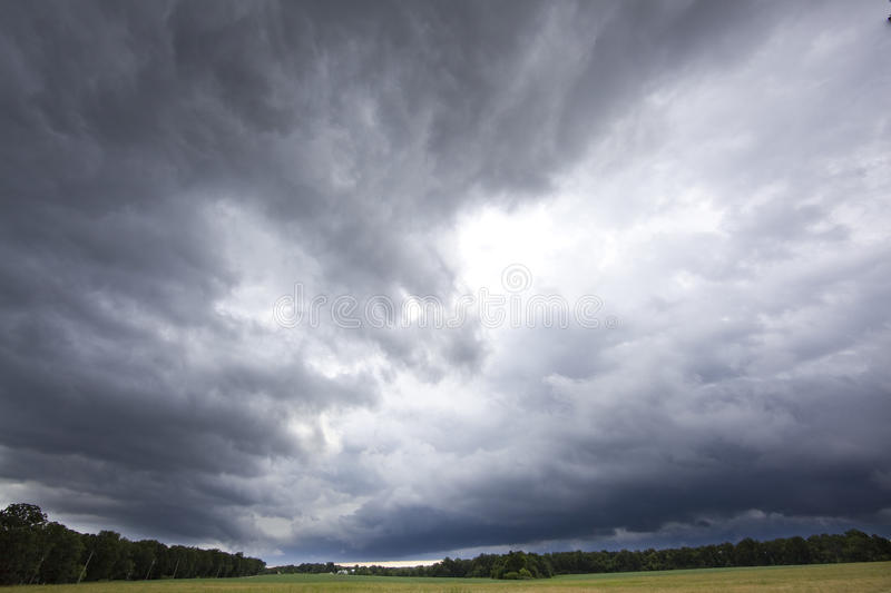 Storm clouds over open field royalty free stock photo