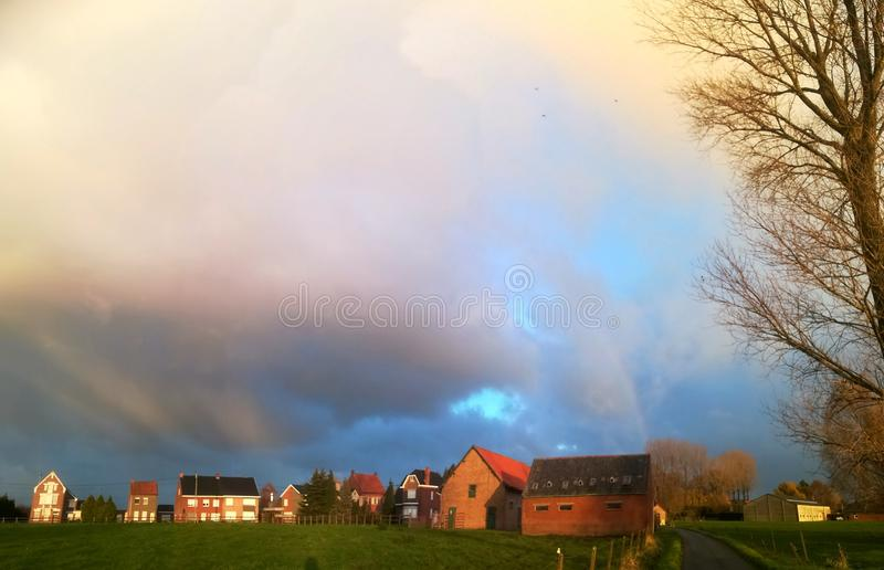 Storm clouds over small village with rainbow stock images