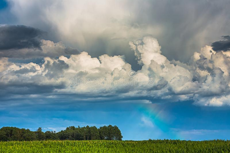 Storm clouds with rainbow part and sunrays stock photography