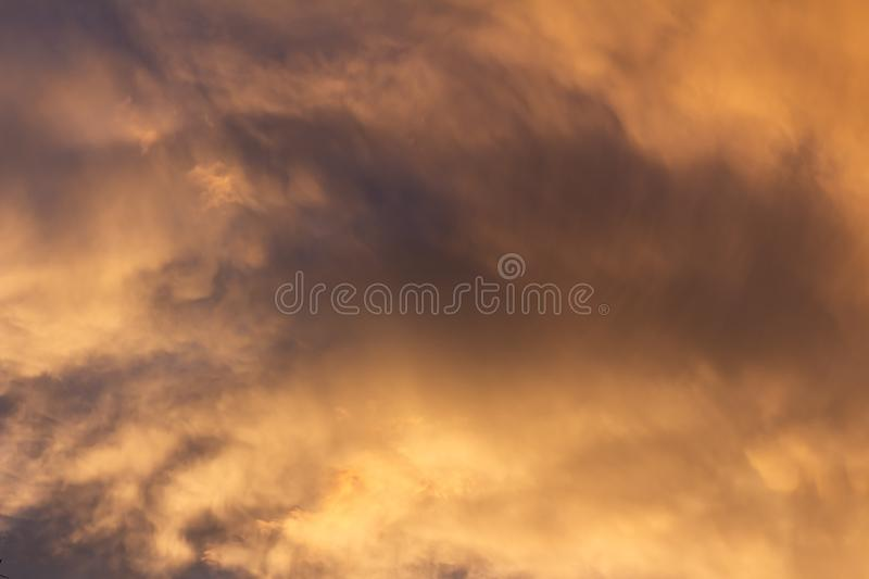 Storm clouds during sunset dyed golden colors. Climate change concept stock photography