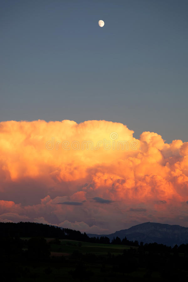 Storm clouds at sunset with moon stock image