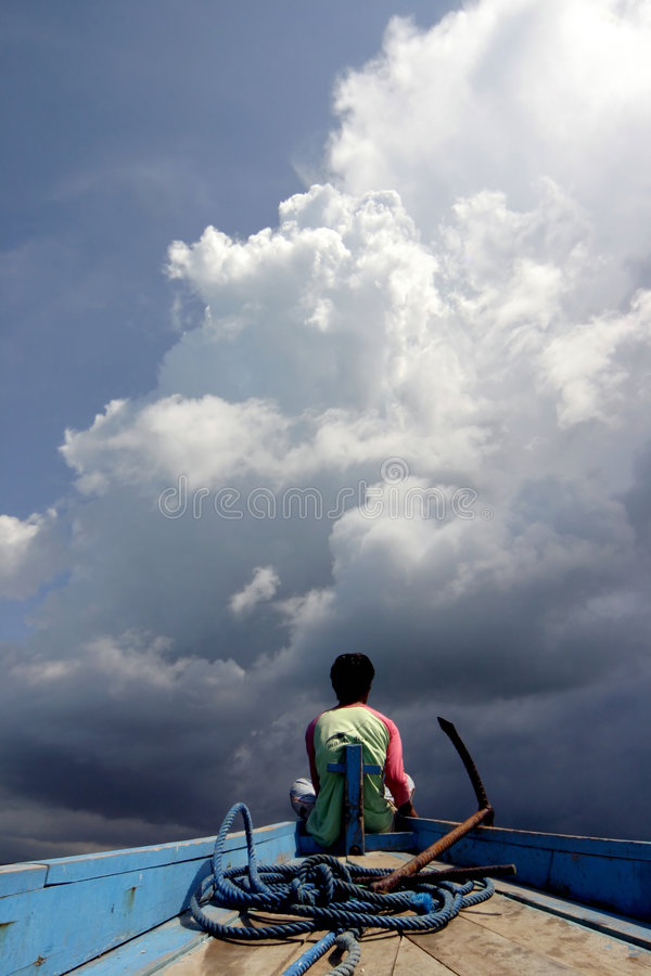 Storm is coming!. Indonesian fisherman sitting on the edge of his boat watching big clouds are coming stock photos
