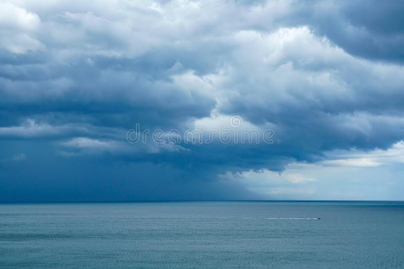 A boat racing to get back to the marina before the storm. A storm coming and a boat racing back to its marina to keep out of the storms path stock photography