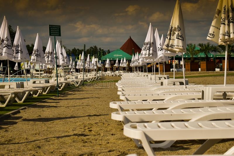 The storm is coming over the beach chairs and umbrella. Dramatic storm waiting scene with no people. Ramnicu Valcea, Romania - 22. 05.2019 stock images