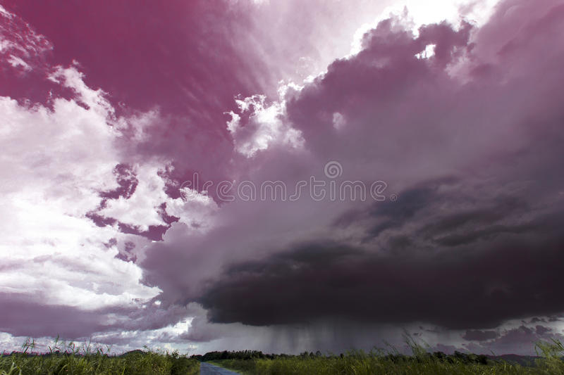 Storm is coming raining ahead shown level of rain cloud lower than good weather cloud over the road and green yellow field can be royalty free stock photos