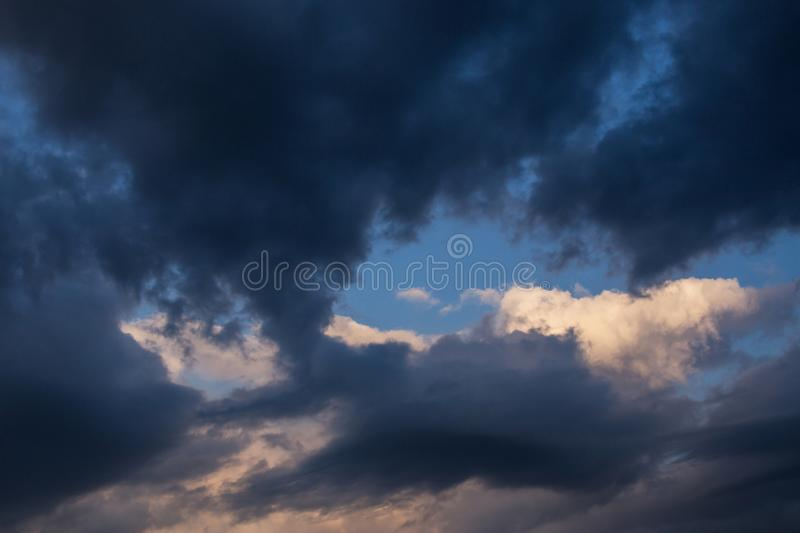 Storm dark clouds against blue sky background. Darkness and light, heaven. Epic dramatic storm dark clouds against blue sky background. Darkness and light royalty free stock photography