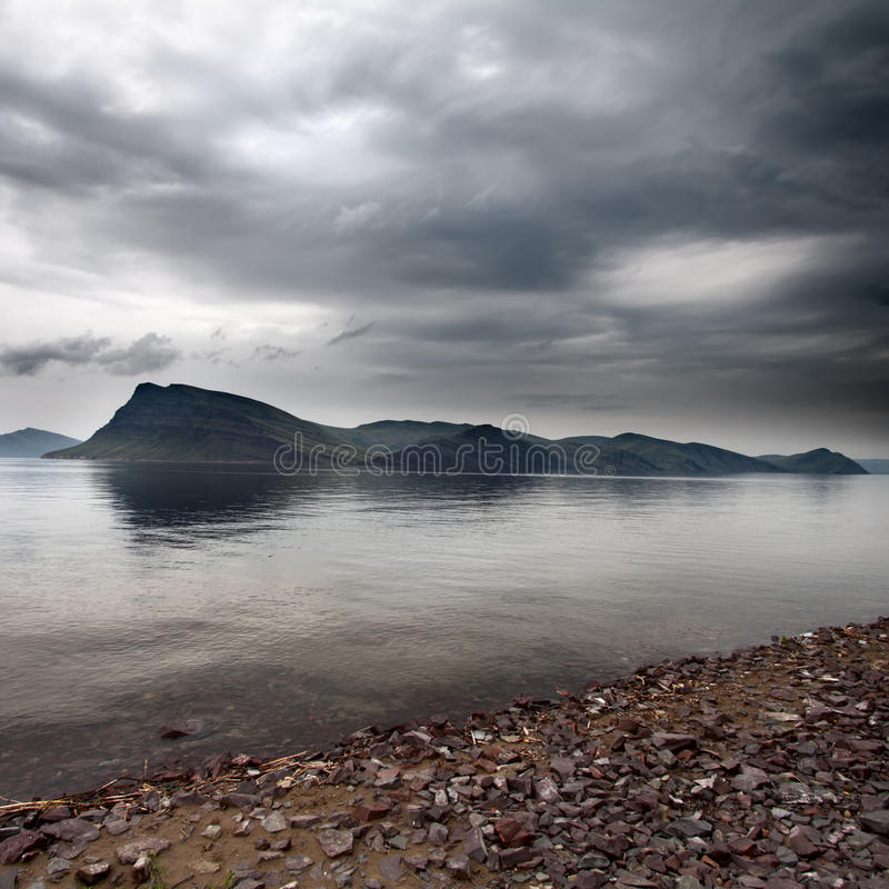 Storm dark clouds over the island in sea. Storm clouds over the island in sea stock images