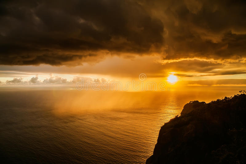 Storm dark clouds at sunset above the Atlantic ocean stock photography