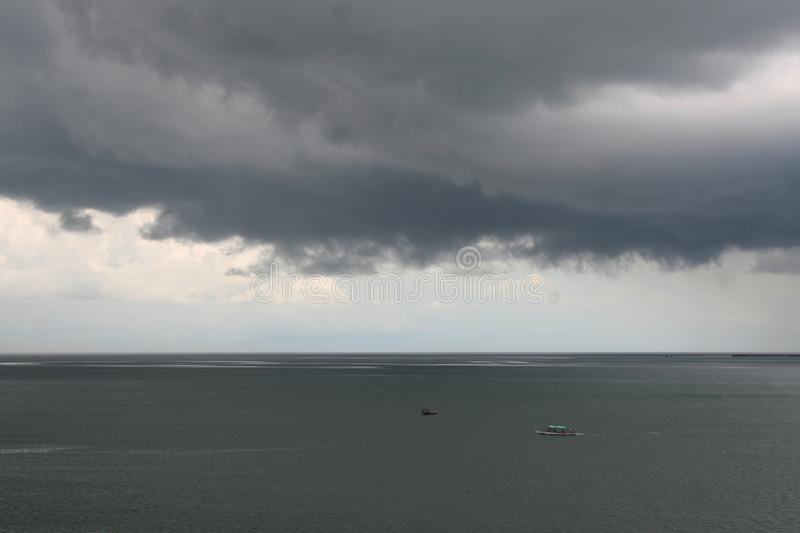 Storm gray clouds over calm gray sea. Natural background royalty free stock photography