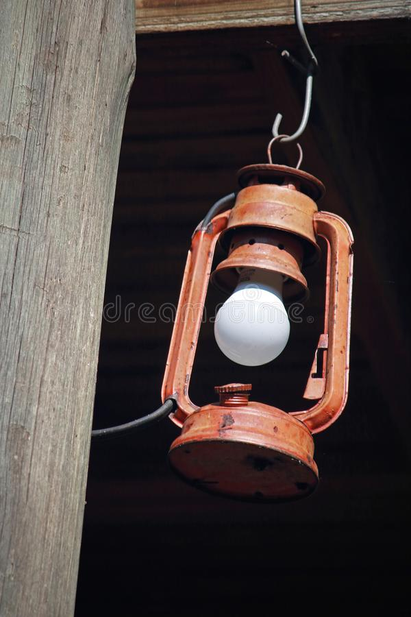 STORM LAMP HANGING FROM A WOODEN BEAM stock photo