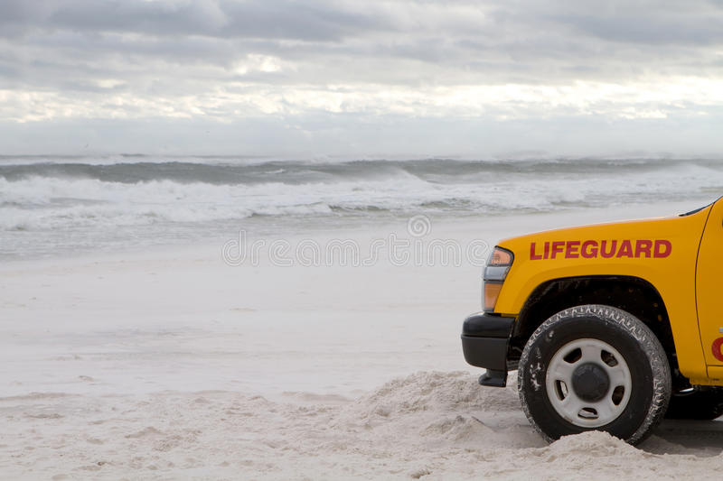 Storm Lifeguard Truck. Lifeguard truck is parked on the beach as tropical storm generated waves come ashore to warn swimmers about the dangerous surf royalty free stock images