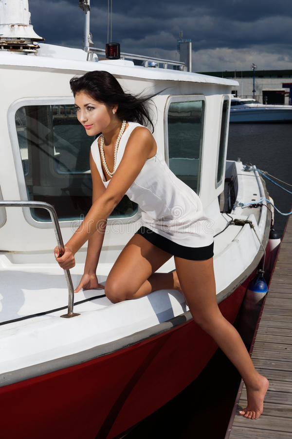 Storm is not an issue. All on board!. Young lady is ready to departure on shaky boat in stormy weather royalty free stock images