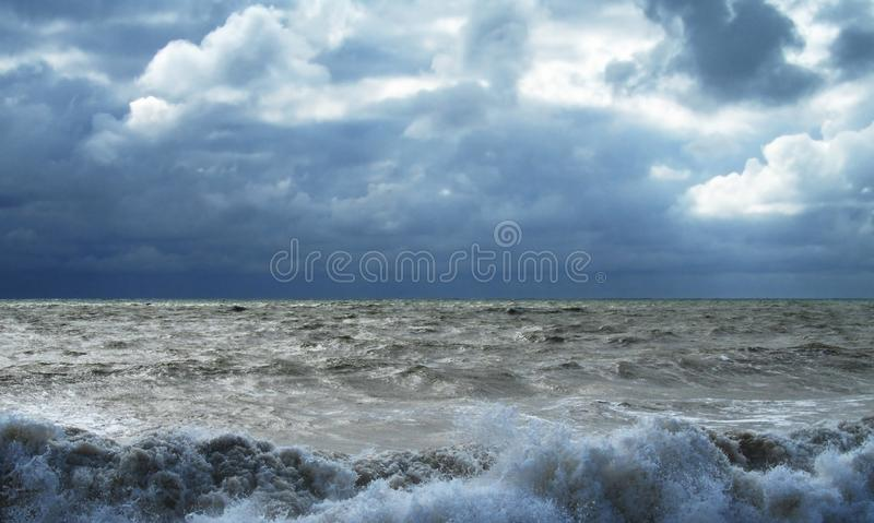 Storm in the ocean. Cloudy gloomy sky and high waves of the surf stock photo