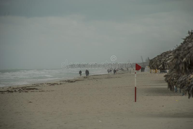 Storm in the ocean posted a red flag on the beach royalty free stock images