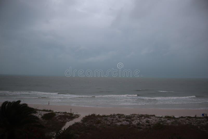 Storm p? stranden Haven rasar, och himlarna visar den tropiska stormen, som makten av naturen visas palmtr?dpu fotografering för bildbyråer