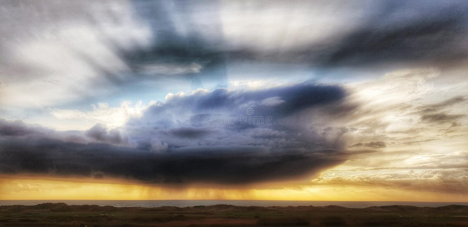 Storm rain cloud at sunset. Storm y storm rain cloud and other clouds at sunset overlooking golf course and ocean of Cardigan Bay, Wales, UK royalty free stock images