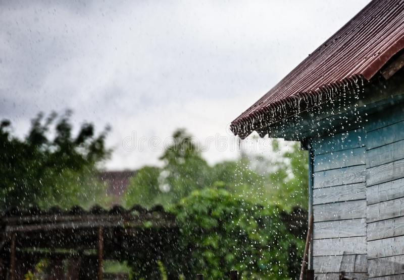 Storm rain drips down from the roof.  stock photo