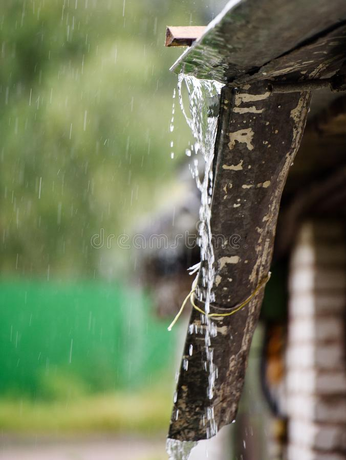 Storm rain drips down from the roof.  royalty free stock photography