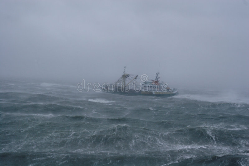 Storm,rain and a fishing boat. During a heavy storm with rain, a fishing-boat comes back from the sea stock photo