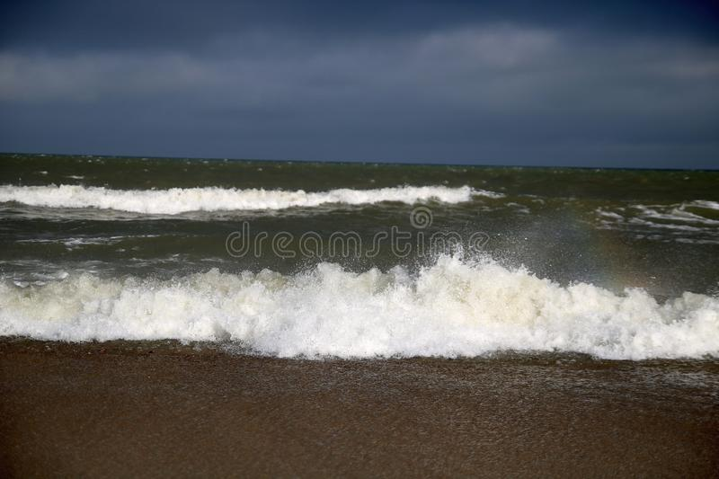 Storm, rainbow, big waves over the Baltic Sea stock images