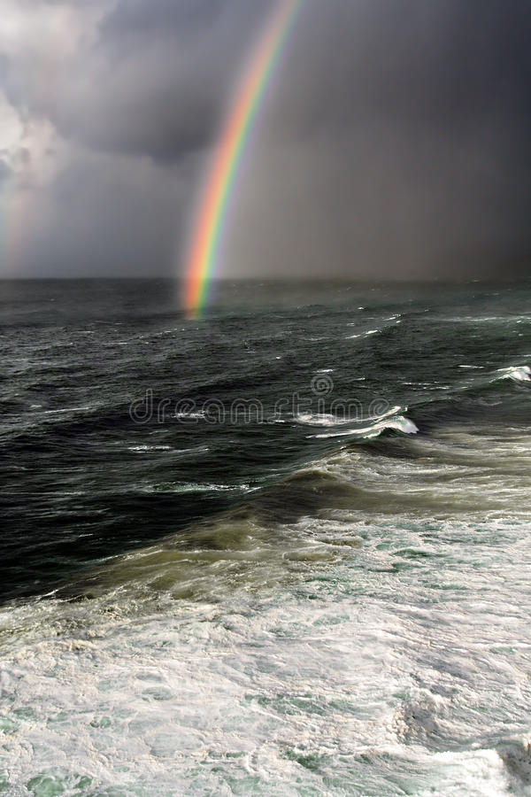 Storm with rainbow and rough sea royalty free stock photography