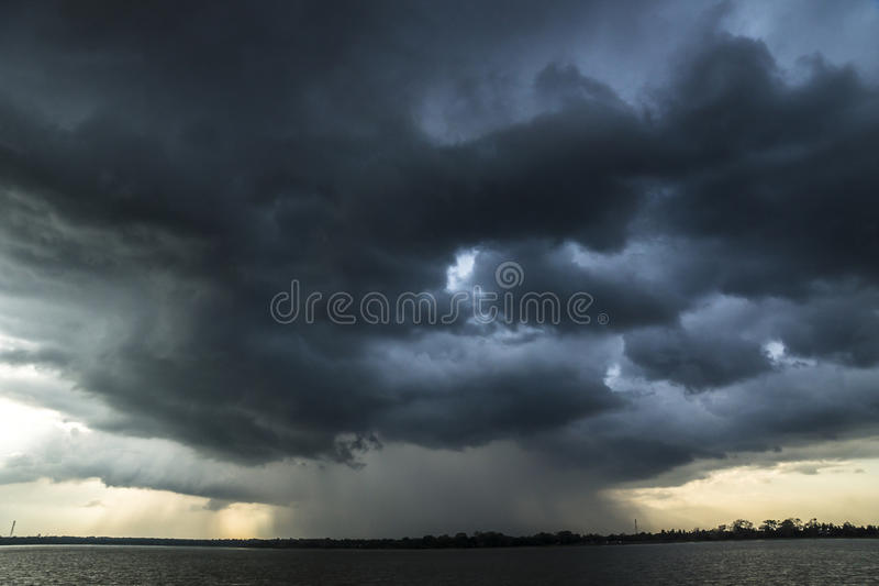 Storm and raincloud over lake in Sri Lanka. Storm arriving over a lake stock image